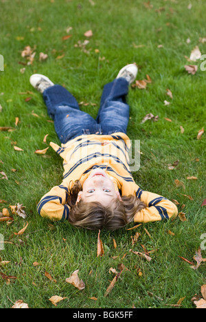 Boy lying on grass Banque D'Images