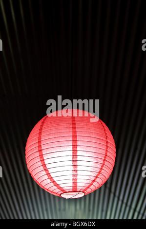 Luminaire rouge contre les lignes d'un toit en tôle ondulée Banque D'Images