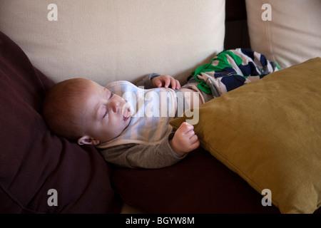 Six mois du garçon endormi sur le canapé. Londres, Angleterre. Banque D'Images