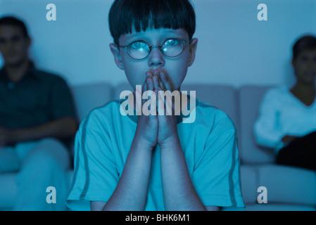 Garçon regarder la TV avec les mains jointes sur la bouche Banque D'Images