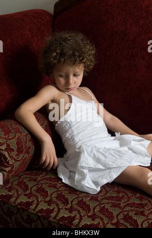 Triste petite fille s'assit sur le canapé en regardant Beyrouth Liban Moyen Orient Banque D'Images