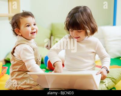 Female toddler et 2-3 ans fille jouant avec l'ordinateur en maternelle. La forme horizontale Banque D'Images