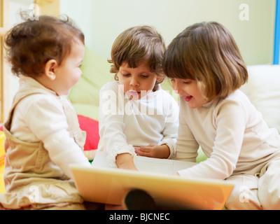 Enfant de sexe féminin et de 2 à 3 ans pour jouer avec l'ordinateur en maternelle et de sourire. La forme horizontale Banque D'Images