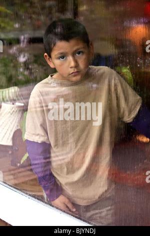 Multi-culturel multiculturel 9 -10 ans ans Hispanic boy looking out par la fenêtre un jour de pluie. Visage triste Banque D'Images