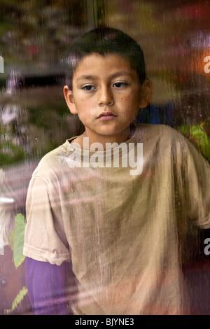 Multicultural multi culturel d'enfant 9 -10 ans ans Hispanic boy looking out par la fenêtre un jour de pluie. M. Banque D'Images