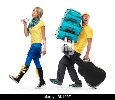 Jeune couple en voyage. Femme marche avec une tasse de café et un homme transportant les bagages. Banque D'Images