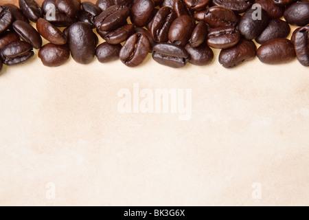 Les grains de café sur un fond de papier parchemin Banque D'Images
