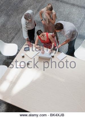 Directement au-dessus de business people using laptop at conference table Banque D'Images
