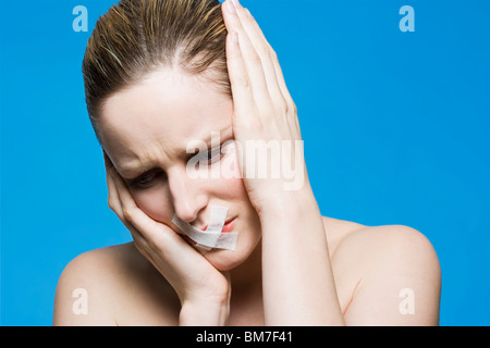 Une femme avec un ruban couvrant sa bouche, tenant sa tête dans la frustration Banque D'Images
