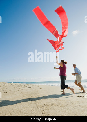 Couple flying kite on beach Banque D'Images