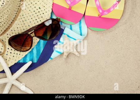 L'été coloré de plage, tongs, serviette, chapeau, lunettes de soleil et d'étoiles de mer sur la plage de sable. Banque D'Images