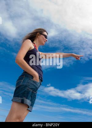 Woman pointing, tenus contre sky Banque D'Images
