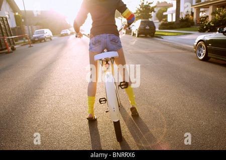 Jeune femme portant des chaussettes jaunes et un hoodie se prépare à lancer un cheval, en vtt. Banque D'Images