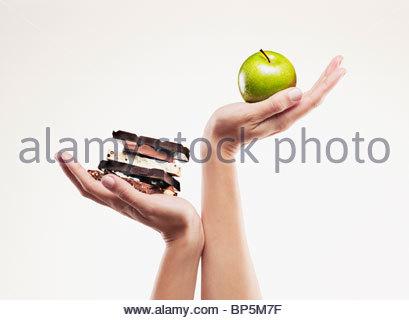Femme prenant la pomme verte au-dessus des barres de chocolat Banque D'Images