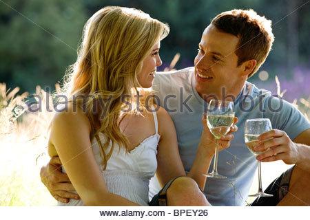 Un jeune couple assis sur l'herbe, boire du vin Banque D'Images