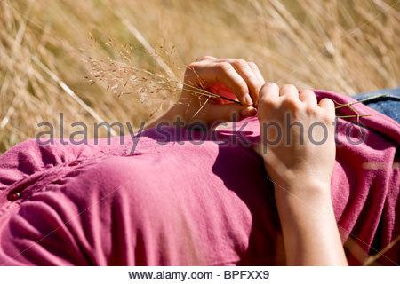 Une femme couchée dans le soleil, tenue d'une herbe, cropped Banque D'Images