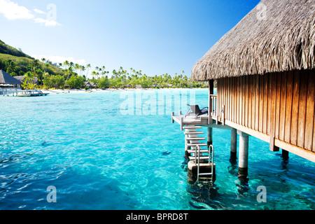 Bungalow sur l'eau avec des marches en incroyable lagon bleu Banque D'Images