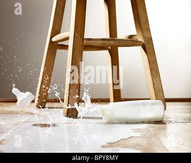 Le biberon et lait renversé avec splash sur un marbre Banque D'Images