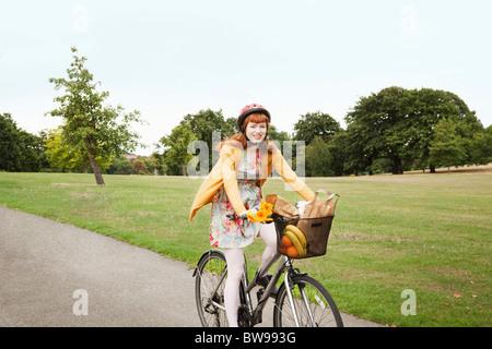 Jeune femme vélo à travers park Banque D'Images