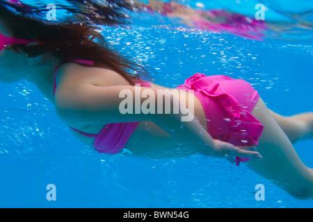 Bikini rose petite fille sous-marine en piscine piscine bleu Banque D'Images