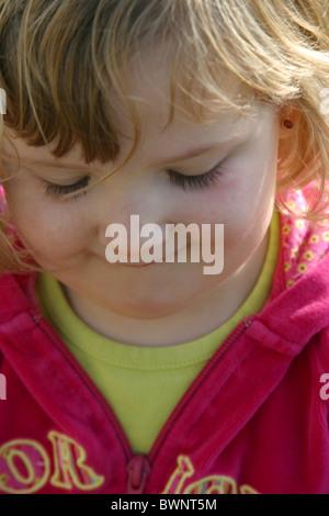 Smiling little girl 3 ans à la baisse, pourrait avoir honte ou peur Banque D'Images