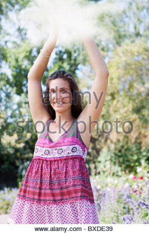 Smiling woman holding mirror in park Banque D'Images