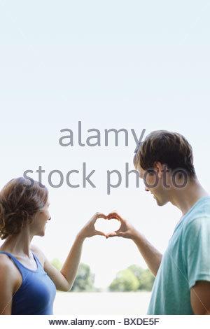 Smiling couple en utilisant les mains pour prendre forme de coeur Banque D'Images