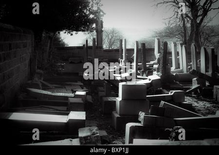 Vieux cimetière en ruines avec déboulonnée et broken head stones. Banque D'Images