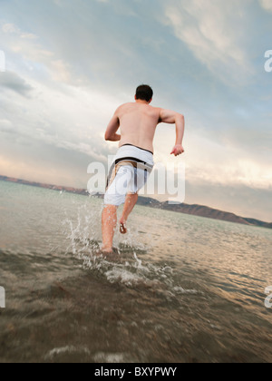 Man running on beach Banque D'Images