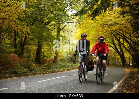 Couple à vélo sur route de campagne Banque D'Images
