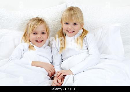 Portrait of cute twins couché dans le lit Banque D'Images