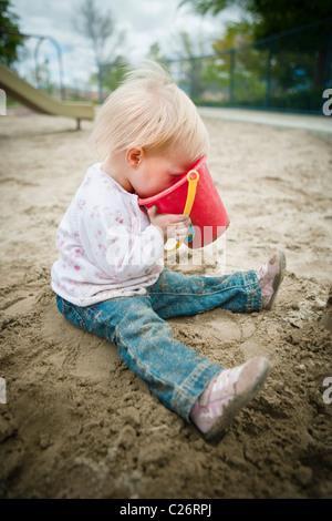1 ans, fille en aire de jeux avec jouets Sable Sandbox Banque D'Images