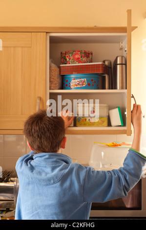 Un modèle photo parution d'un garçon de onze ans à la recherche dans les armoires de cuisine pour trouver de la Banque D'Images