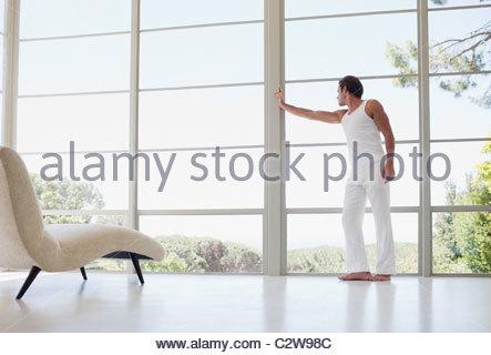 L'homme appuyé contre la fenêtre et regardant Banque D'Images