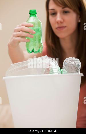 Studio shot of woman (8-9) mise en bouteille en plastique bac de recyclage Banque D'Images
