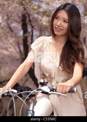Young smiling woman sitting in a park passé cerisiers en fleurs Banque D'Images