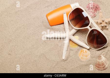 Bouteille de solaire baume avec des coquilles et des lunettes de soleil sur le sable Banque D'Images