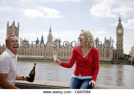 Un couple devant les Chambres du Parlement, l'ouverture d'une bouteille de champagne Banque D'Images