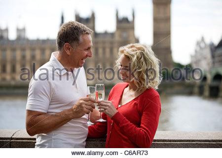Un couple devant les Chambres du Parlement, toasting with champagne Banque D'Images