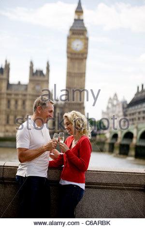 Un couple devant les Chambres du Parlement, drinking champagne Banque D'Images