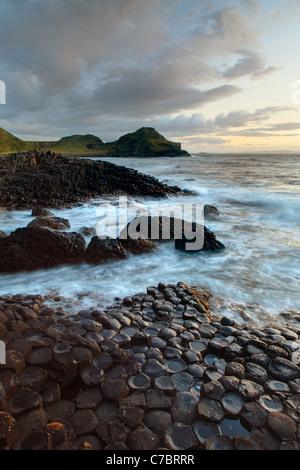Plus d'éclaboussures des vagues colonnes basaltiques près de Sunset, Giant's Causeway, comté d'Antrim, en Irlande Banque D'Images