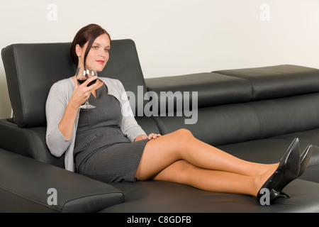 Elegant businesswoman sitting on sofa en cuir verre vin rouge Banque D'Images