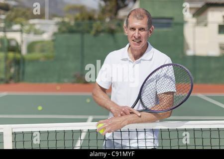 Vieil homme debout sur un court de tennis Banque D'Images