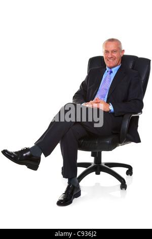 Photo d'un homme d'âge mûr portant un costume et cravate, assis dans un fauteuil en cuir avec ses jambes croisées Banque D'Images