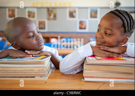 Boy and girl leaning on books at desk in classroom, Johannesburg, la Province de Gauteng, Afrique du Sud Banque D'Images
