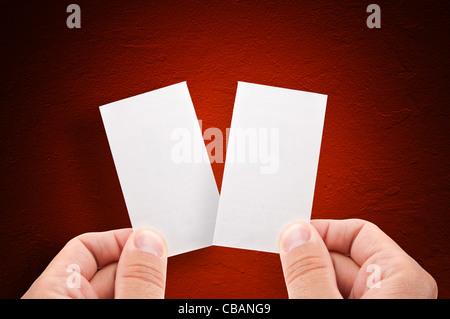 Mains tenant plus de cartes d'affaires vide grungy red background Banque D'Images