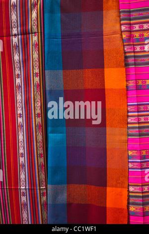 Une variété de tissu très coloré est suspendu dans un affichage dans le marché d'Otavalo, Équateur. Banque D'Images