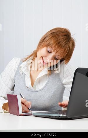 Happy girl attrayant à parler au téléphone et écrit simultanément Banque D'Images
