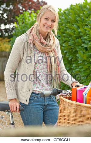 Portrait of smiling young woman with bicycle et les manuels scolaires dans panier Banque D'Images