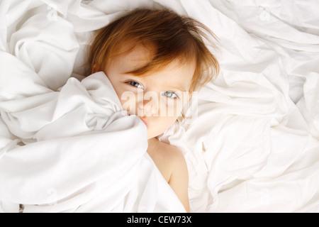 Bel enfant enveloppé dans des draps blancs Banque D'Images